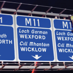 Image of a Worker Erecting an Overhead Sign on a Dual Carriageway propped up by a Crane